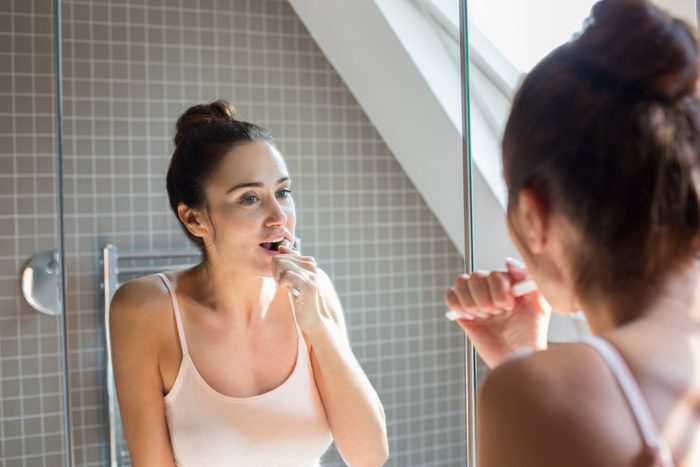 Mid adult woman brushing teeth in bathroom mirror.