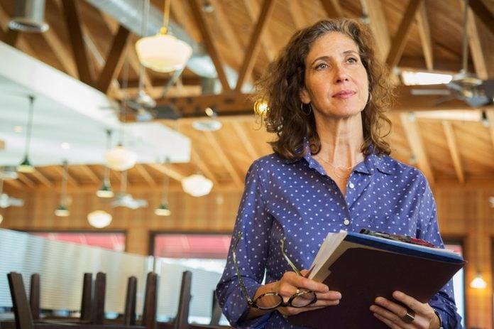 Pensive Caucasian woman holding paperwork in restaurant