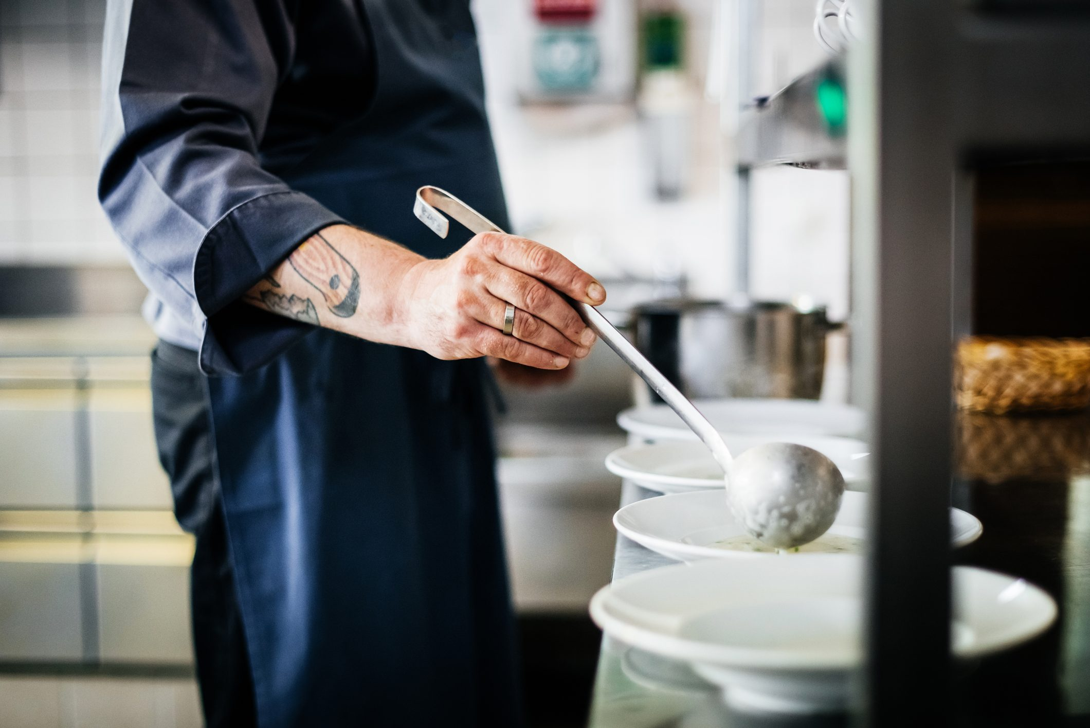 Chef With Tattoos Ladling Soup Into Bowls