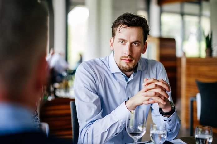 Businessman Listening To Colleagues Over Lunch At Restaurant Table