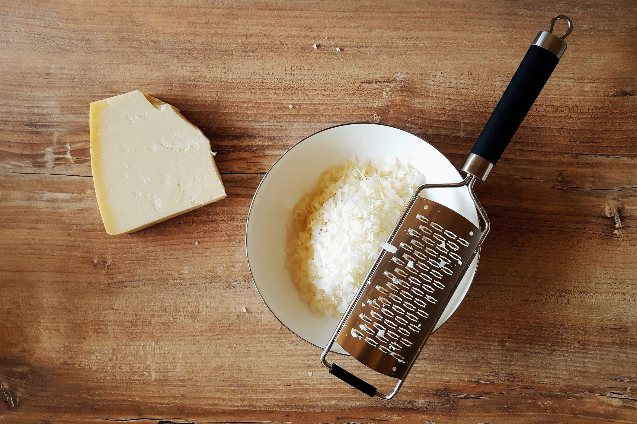 High Angle View Of Cheese With Grater On Wooden Table