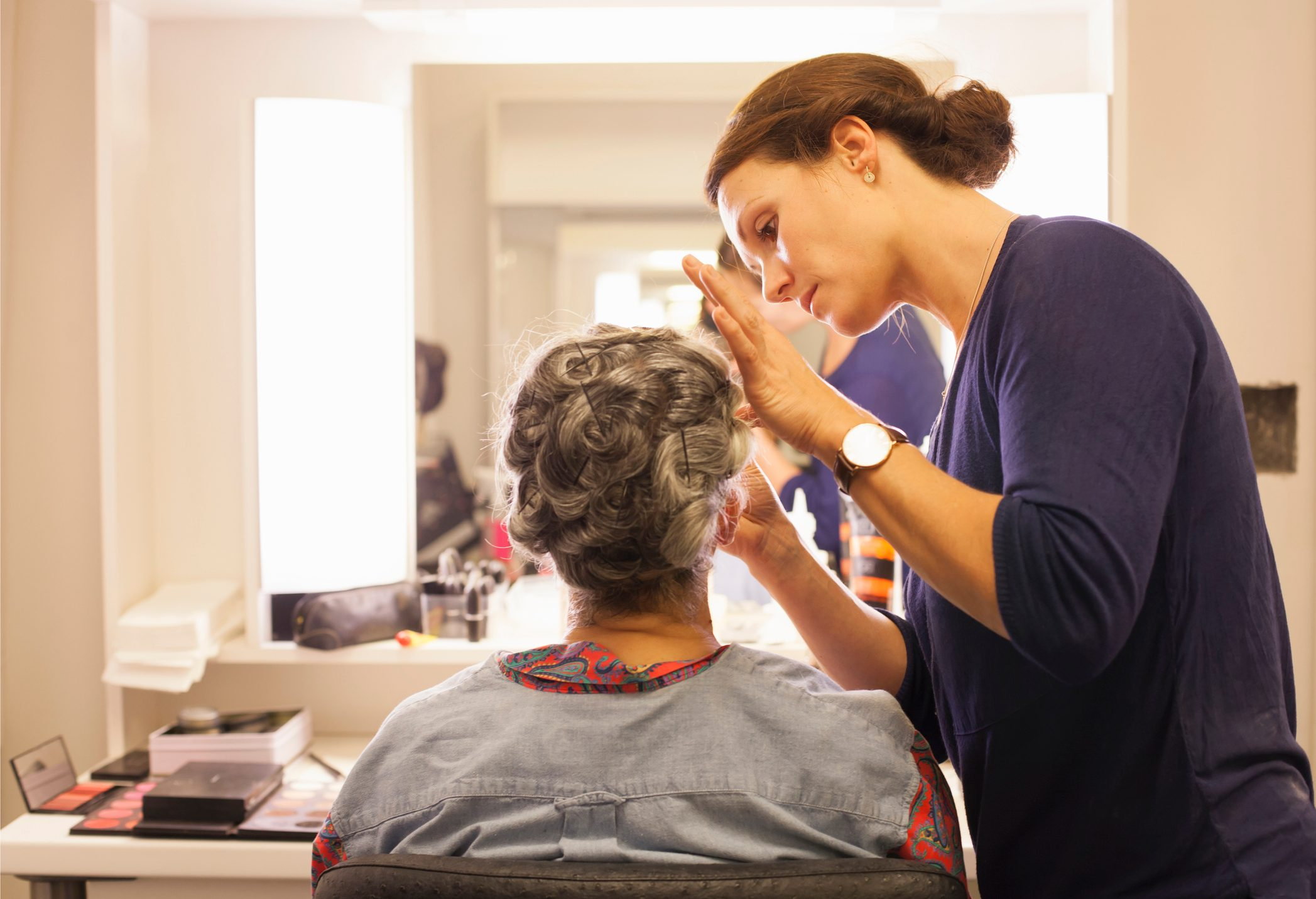 Senior woman having her hair and makeup done by makeup artist before stage performance