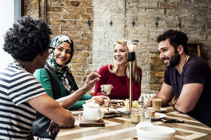 Group of friends sitting in cafe smiling and talking