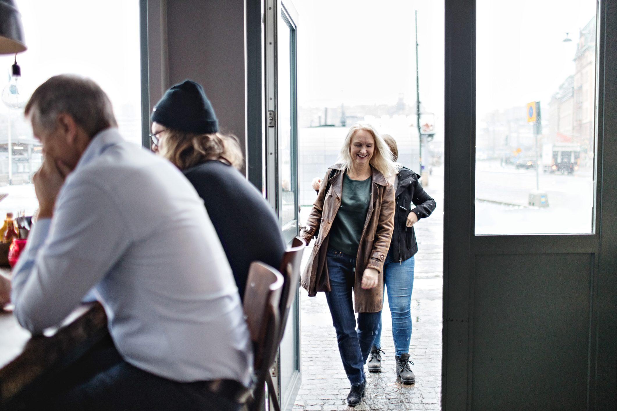 Women entering from open door while men sitting at restaurant