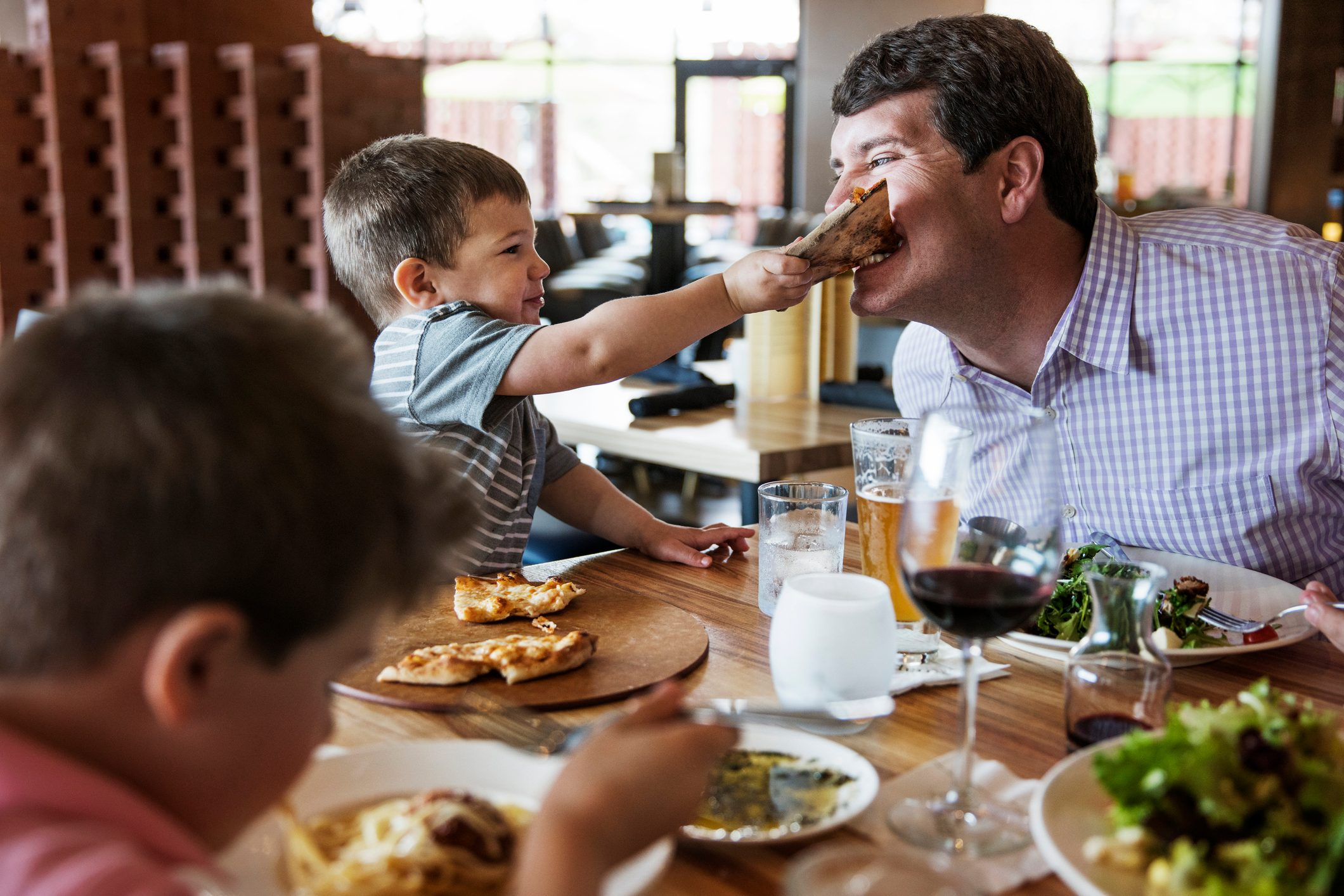 Boy feeding pizza to father in restaurant