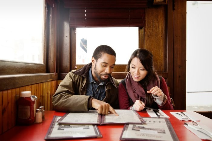 Couple looking at menu while sitting in restaurant