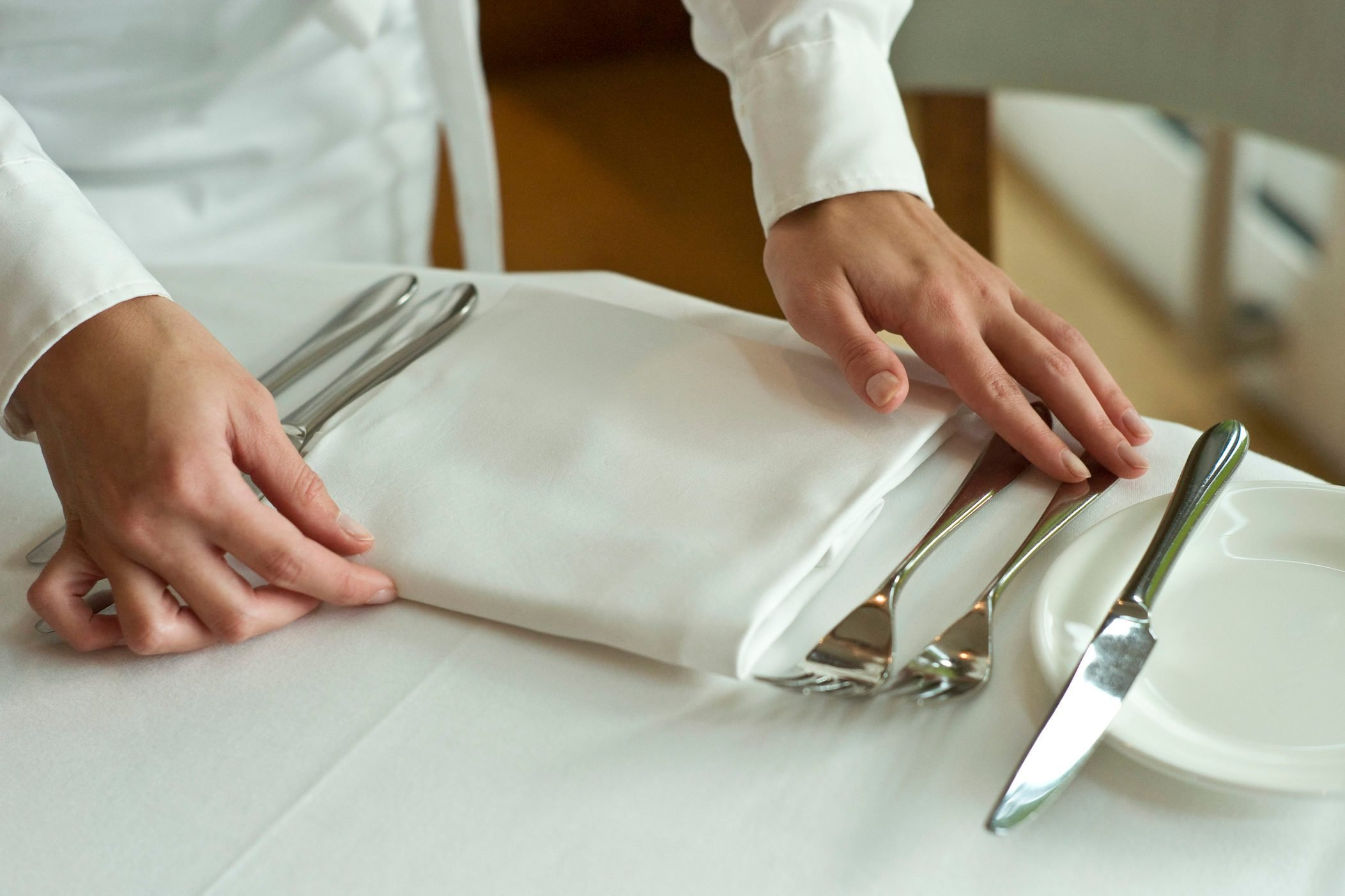 Waitress adjusting table settings in restaurant, mid section