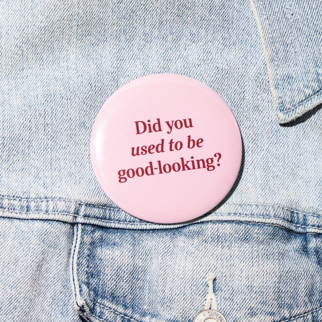 "denim jacket detail with a button that says, ""Did you used to be good looking?"""