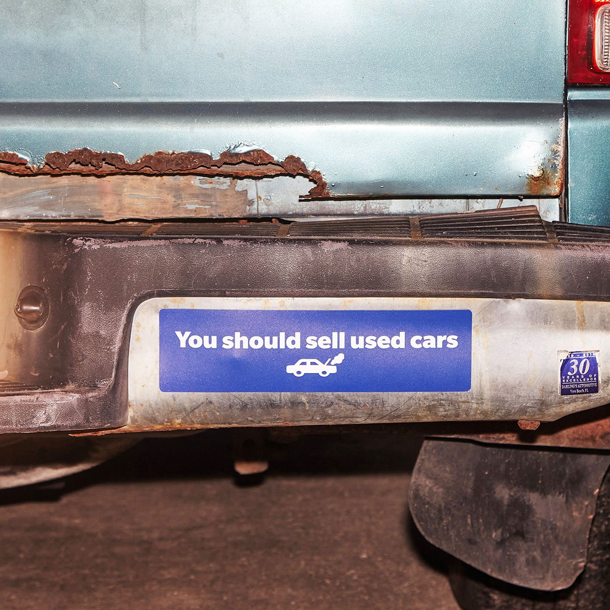 """close up on a bumper sticker that reads, """"You should sell used cars"""""""