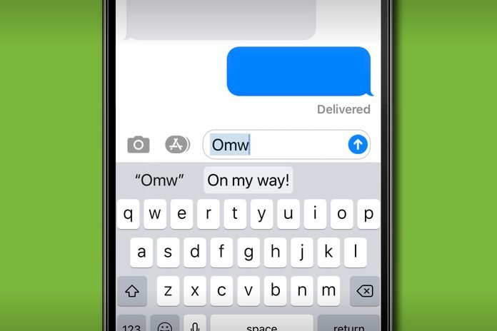 "iPhone keyboard typing ""omw"" and the text auto-correcting to ""on my way!"""