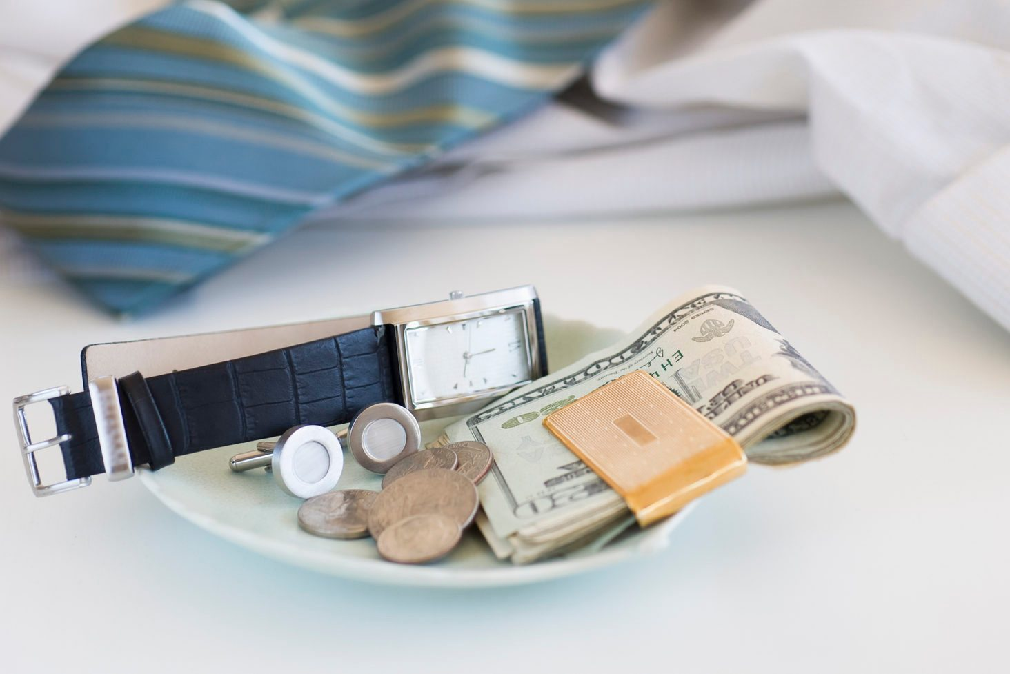 Men's items on a plate on dresser