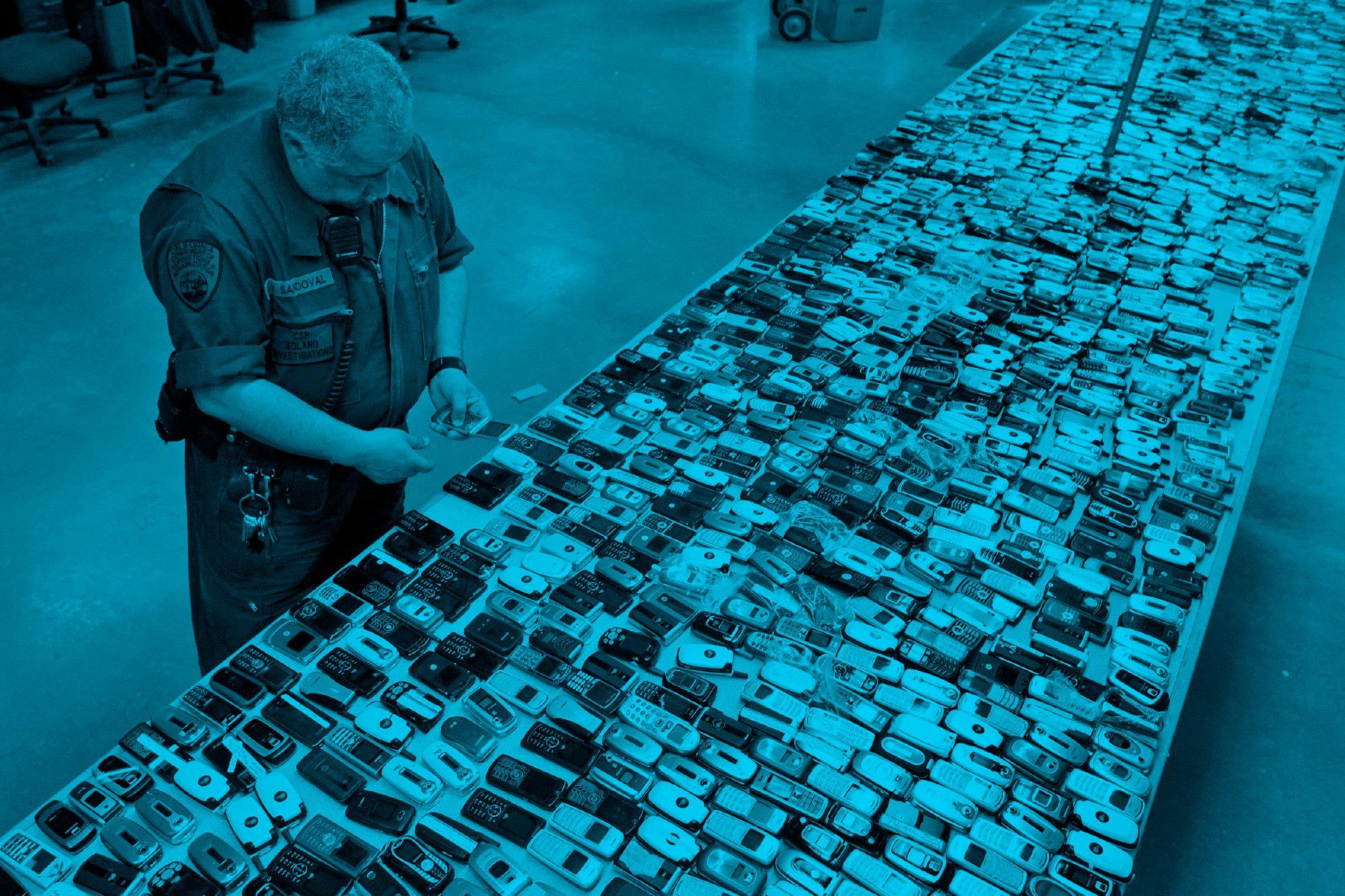thousands of confiscated cell phones laid out on tables