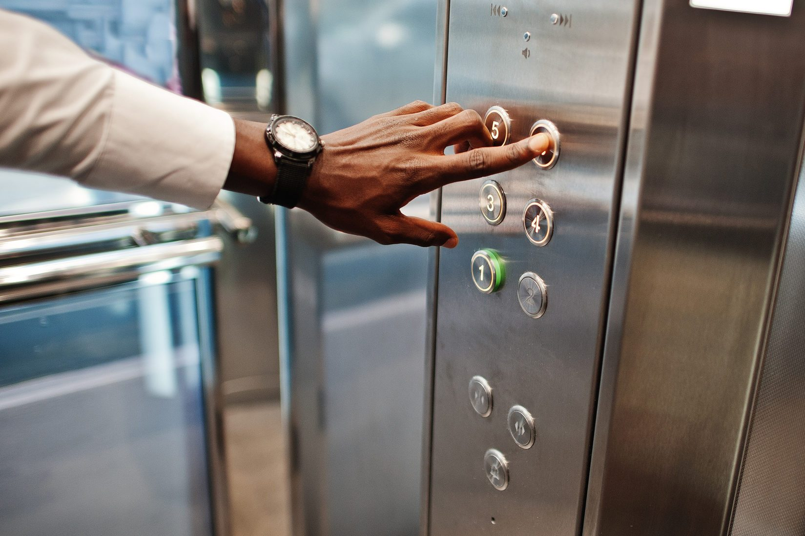 Close up photo of african american man hand with watches at elavator or modern lift, pushing button.