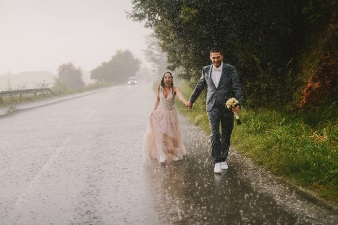 Just married couple holding hands and walking on rain. Walking in wet ceremonial clothes on driveway. Smiling and looking at camera.