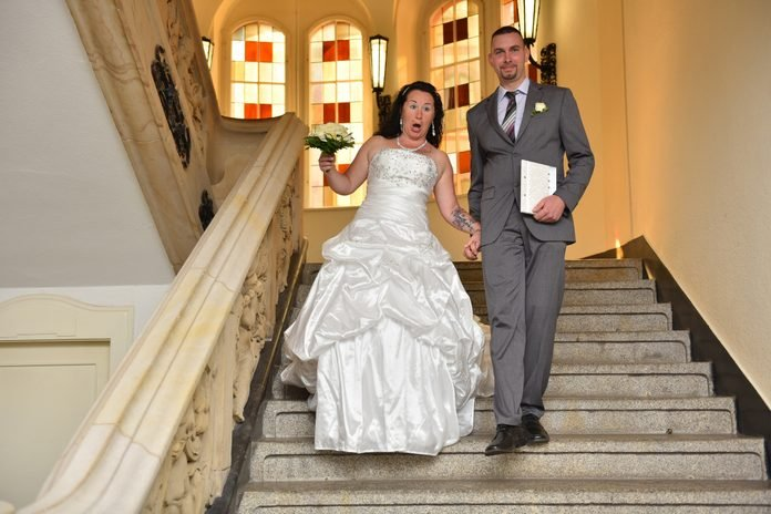 Low Angle View Of Falling Bride Holding Man On Steps