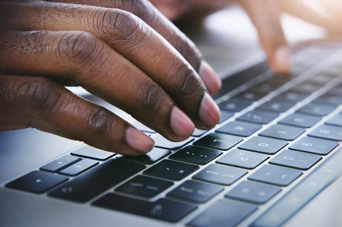 close up of hands on a laptop keyboard
