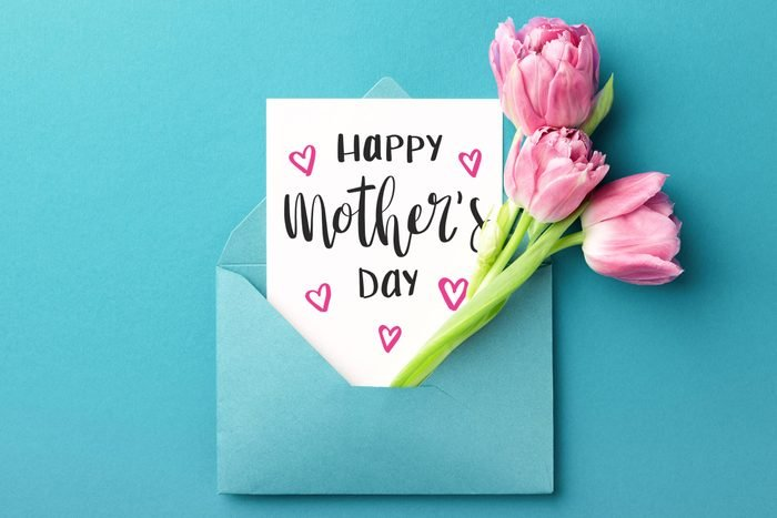 """paper and pink flowers sticking out a blue envelope on blue background. card reads """"Happy Mother's Day"""""""