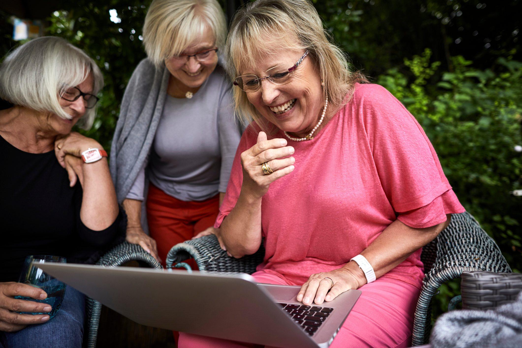 Happy senior women using laptop in garden