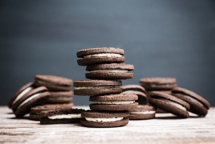 Stack of chocolate sandwich cookies on the rustic wooden background