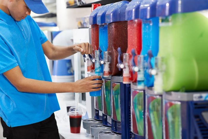 Male employee filling soda in cup from machinery