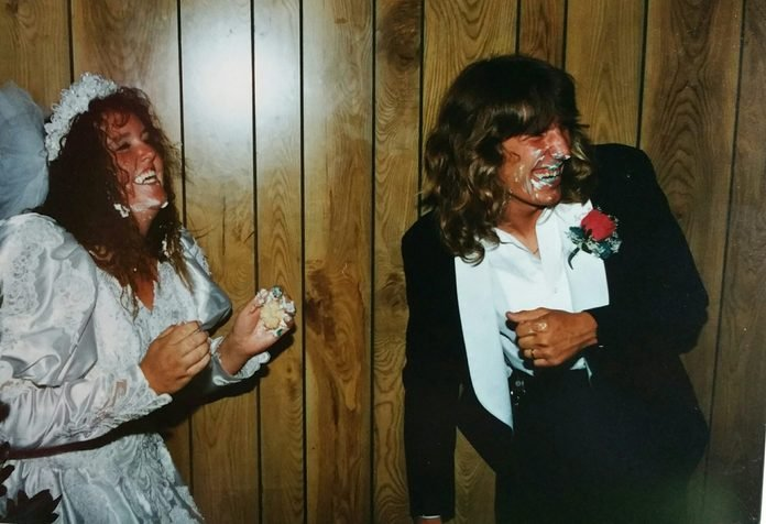 Happy Couple Playing With Cake During Wedding Reception