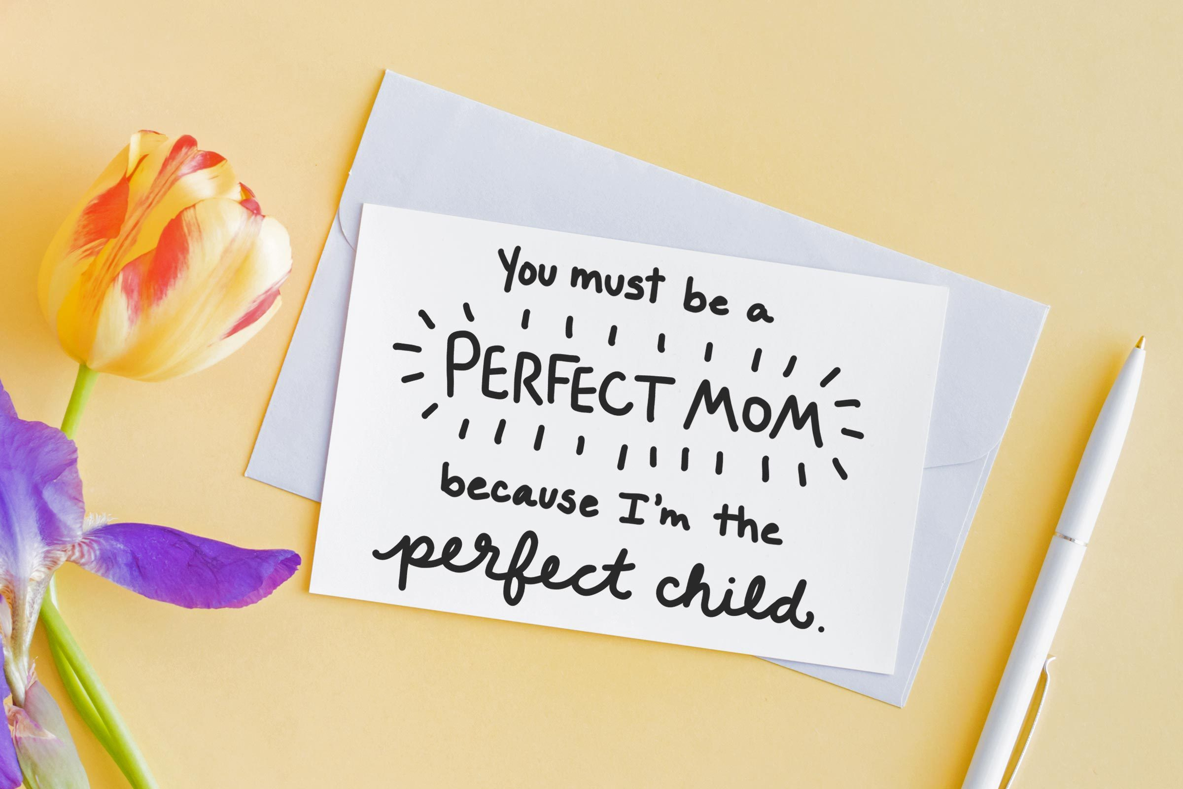 """card, colorful tulip, and pen on orange background. card reads, """"You must be a perfect mom because I'm the perfect child"""""""