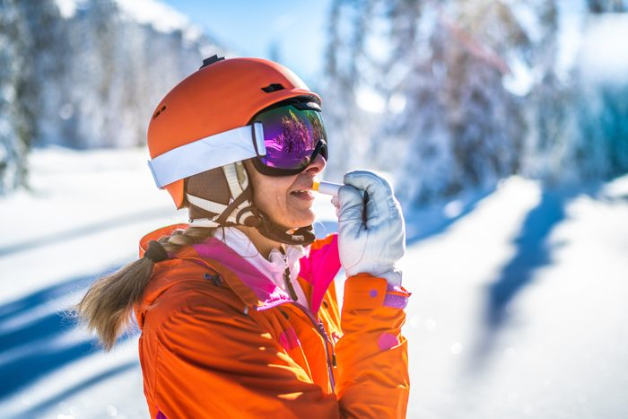 skier woman with skiing helmet putting on sunscreen lip protection