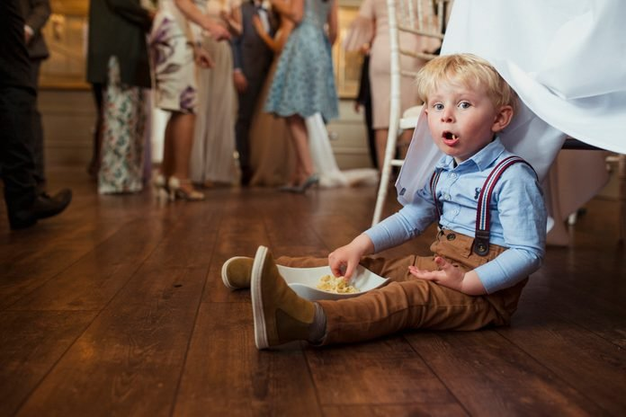Young boy sitting under a table at a wedding reception with a bowl of snacks.