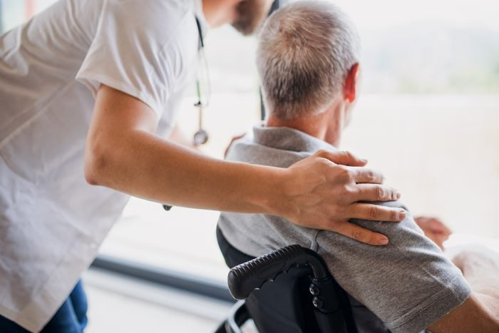 A midsection of male healthcare worker talking to senior man in wheelchair indoors at home.