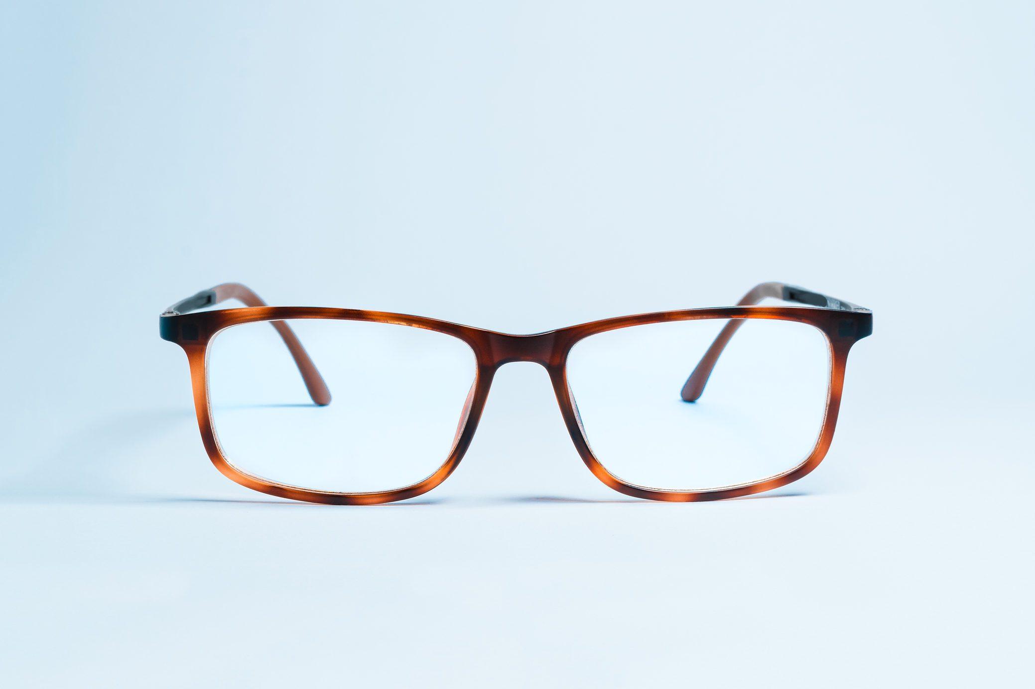 Close-Up Of Eyeglasses Against Blue Background