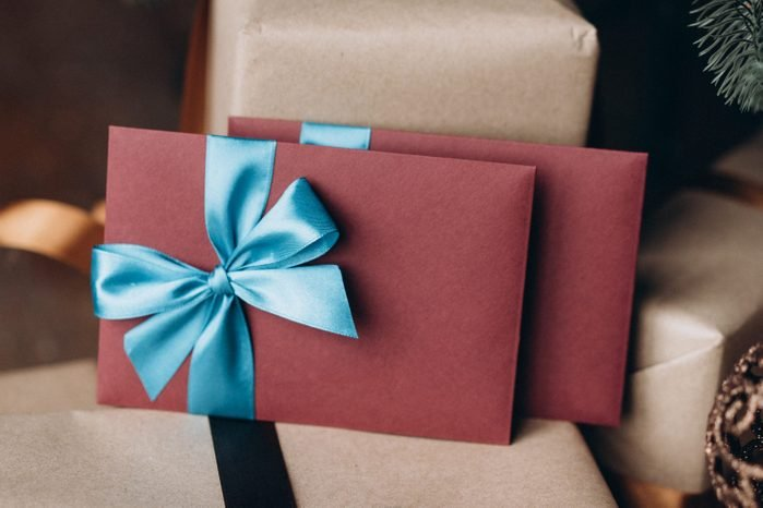 Gift cards in burgundy envelopes with blue bows among other gifts