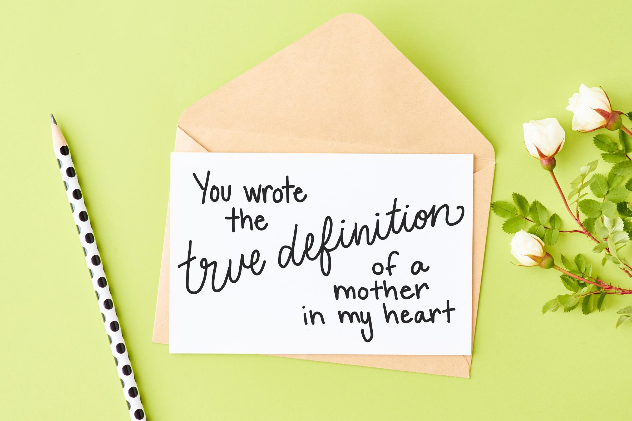 """card, pencil, and flowers on green background. card reads, """"you wrote the true definition of a mother in my heart."""""""