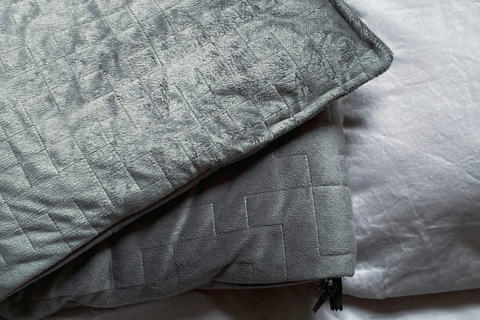 Still Life Of Gray Weighted Blanket In Bedroom
