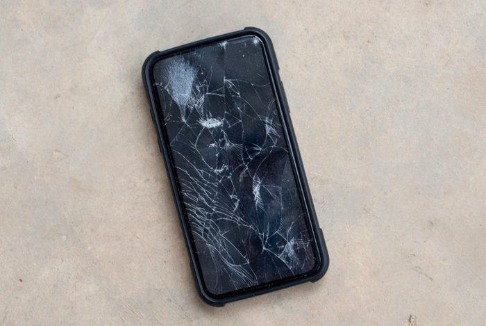 The phone screen is cracked.