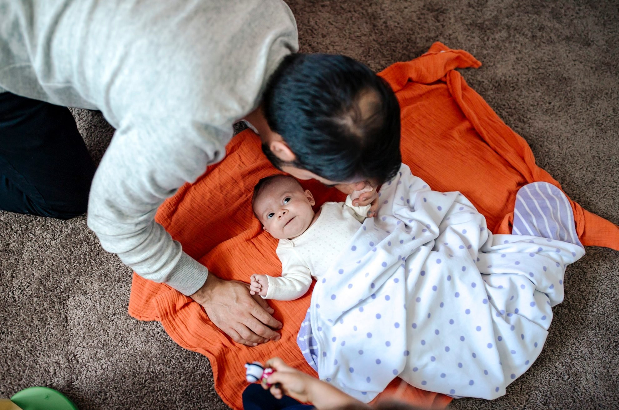 Father leaning over baby on orange blanket on floor