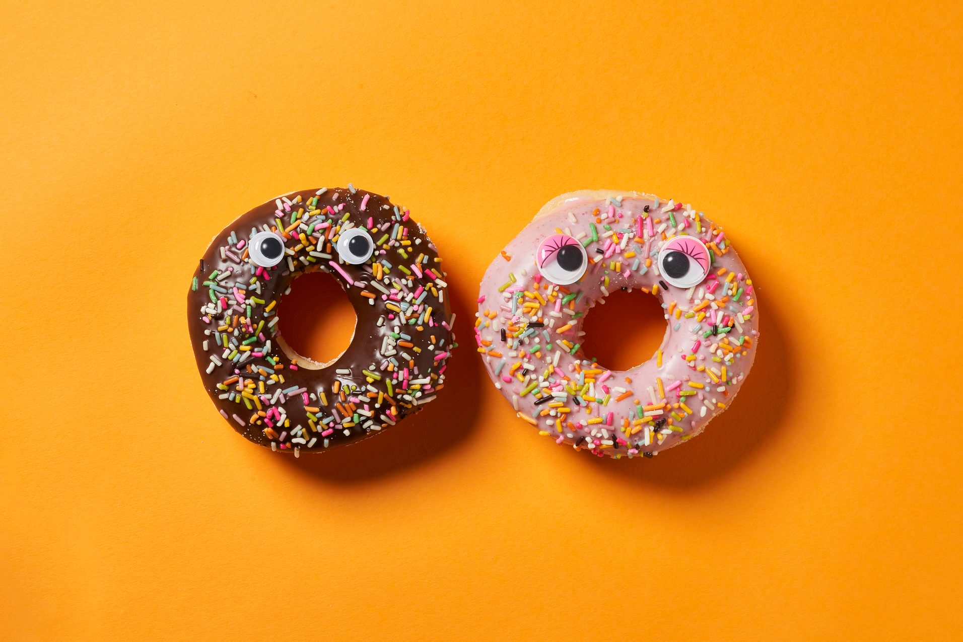 Two Sprinkle Donut with googly eyes on orange background