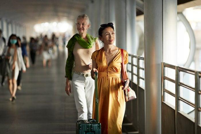 Women walking on bridge at railroad station