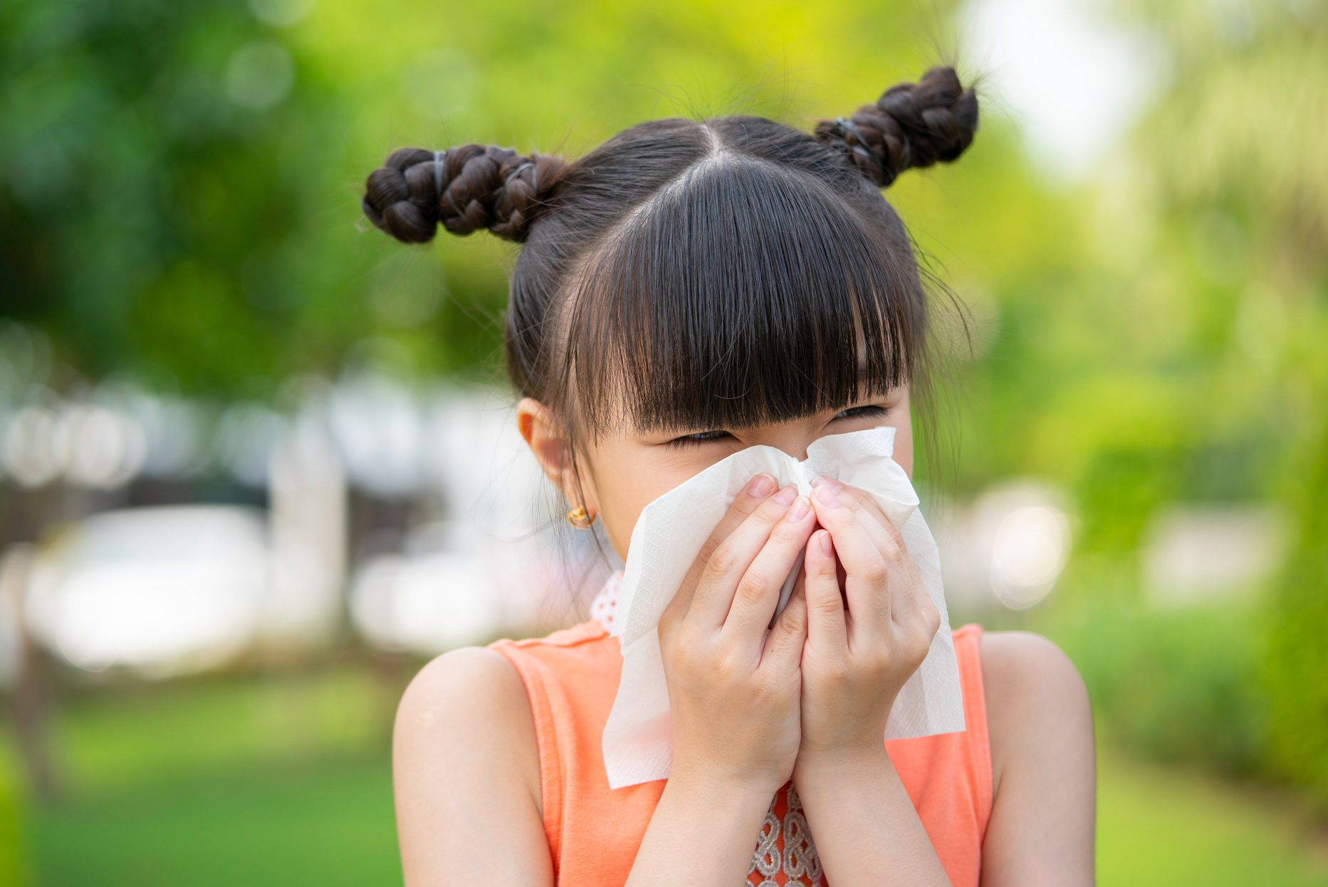 Small girl blowing her nose into a napkin