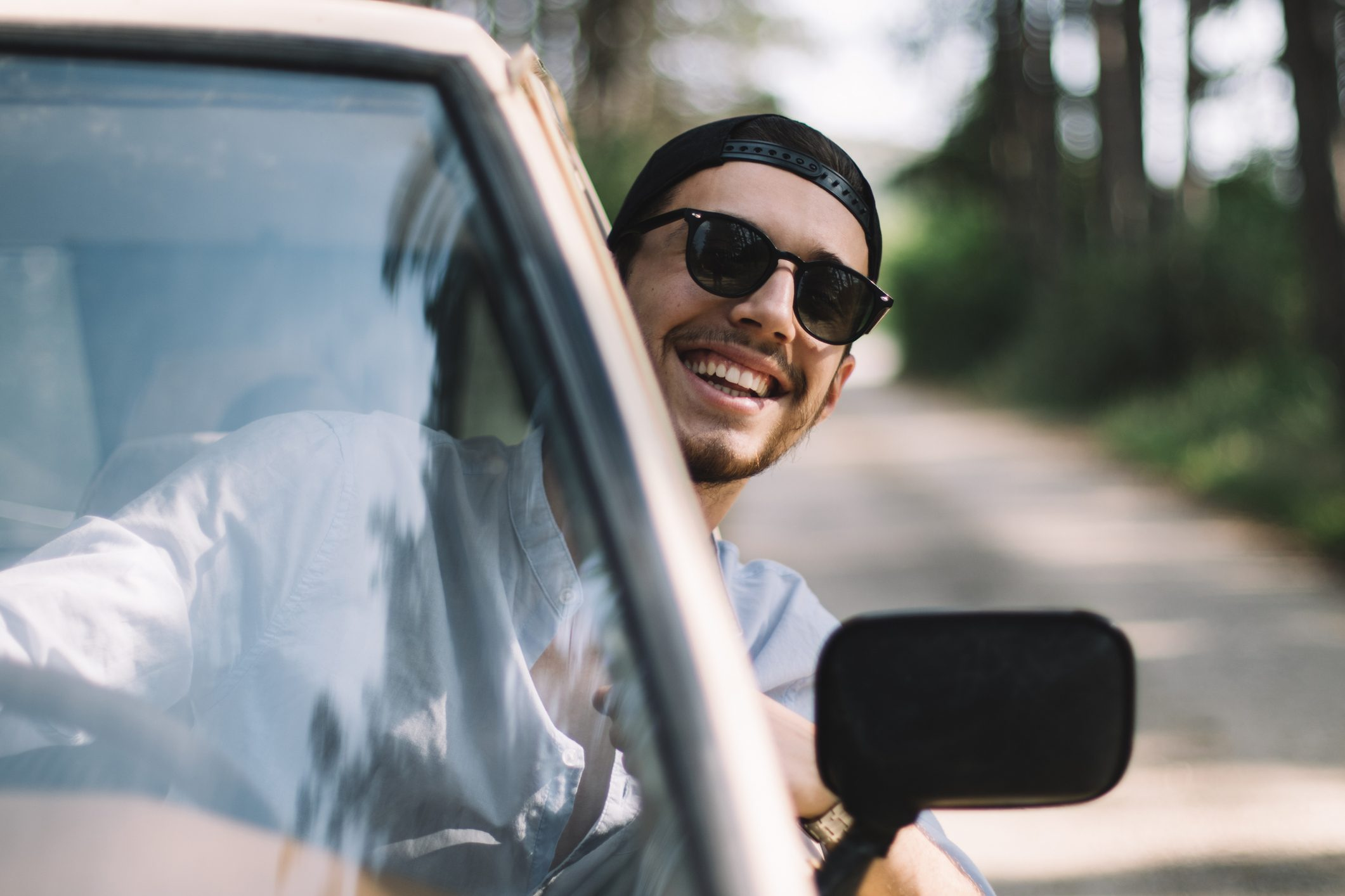 Young man with black hair and sunglasses looking through window of car while driving and smiling at camera