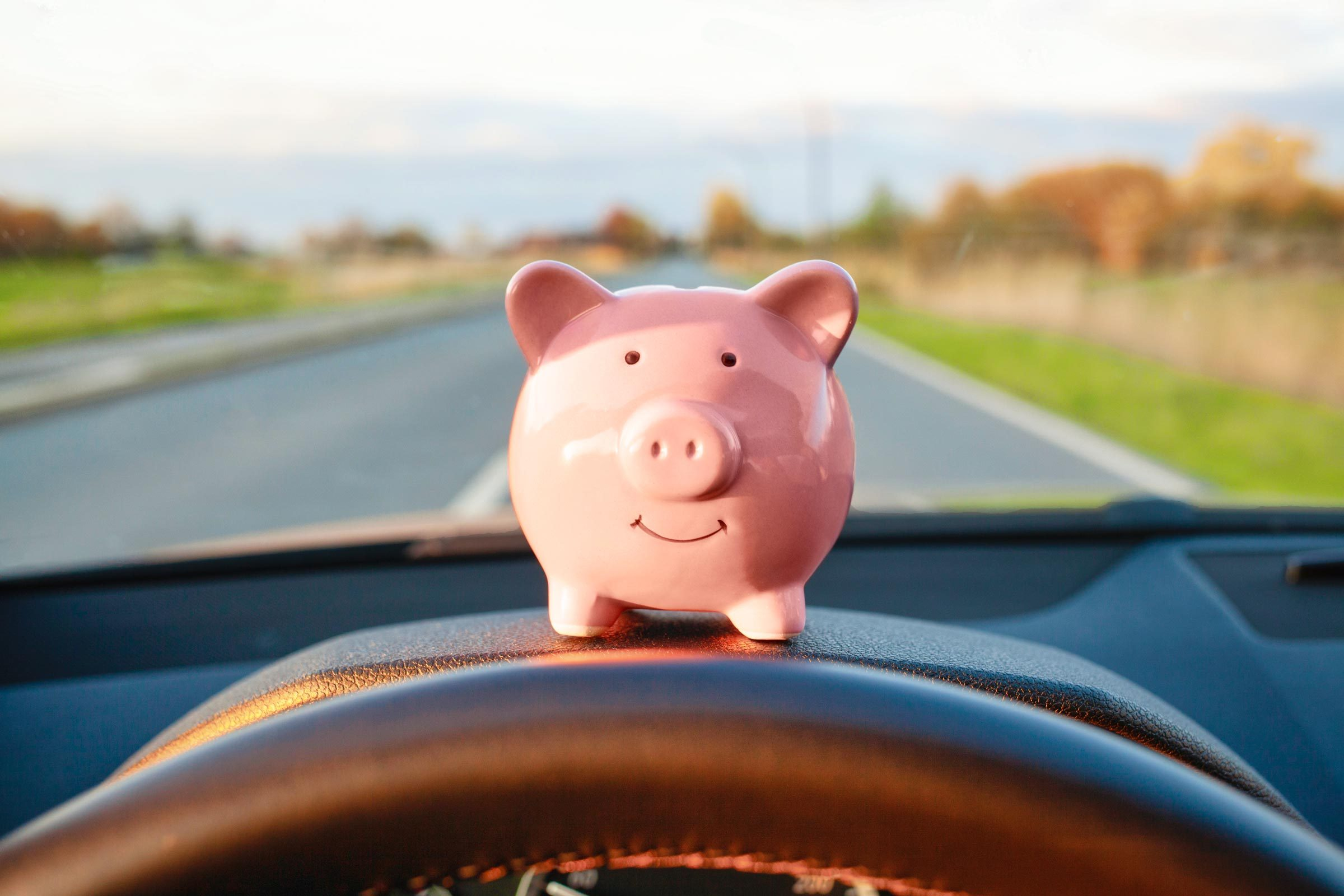 piggy bank sitting on the dashboard of a car on a road trip