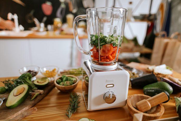 Healthy vegan ingredients in juicer on table