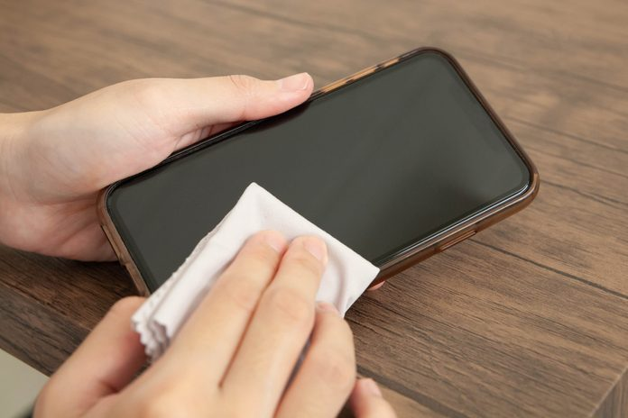 Closeup of hand cleaning smartphone screen with disinfecting wipe on wooden table.