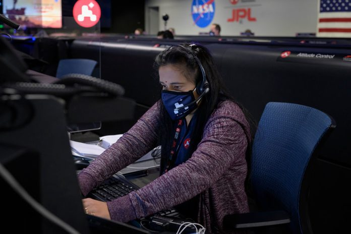 Perseverance Mars rover mission commentator and guidance, navigation, and controls operations Lead Swati Mohan studies data on monitors in mission control, February 18, 2021 at NASA's Jet Propulsion Laboratory in Pasadena, California.