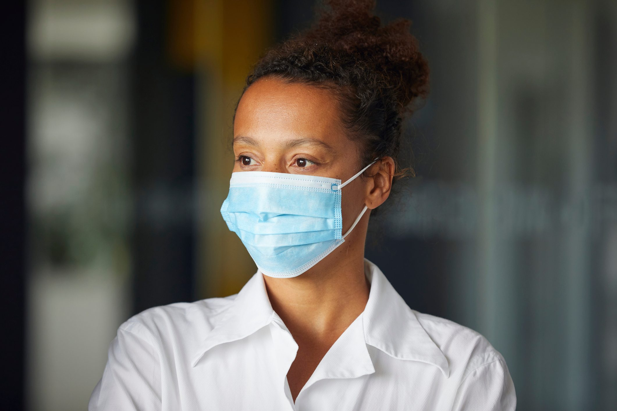 Portrait of businesswoman wearing light blue protective mask looking at distance