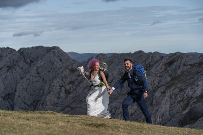 Bridal couple with climbing backpacks walking on meadow