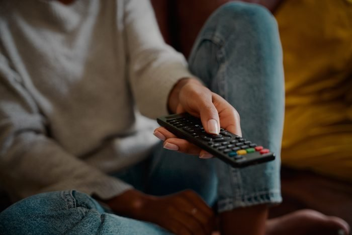 Closeup of young female hand holding remote control and changing channel at home watching television alone