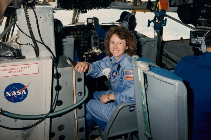 American NASA astronaut Christa McAuliffe smiles, seated near the controls of a Boeing KC-135 Stratotanker flying for the Johnson Space Center from Ellington Field Joint Reserve Base in Houston, Texas, 16th October 1985.