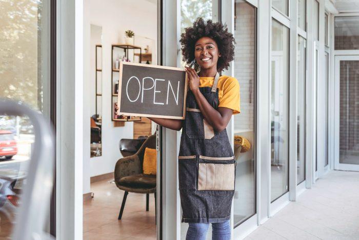 bkack business owner opening her shop