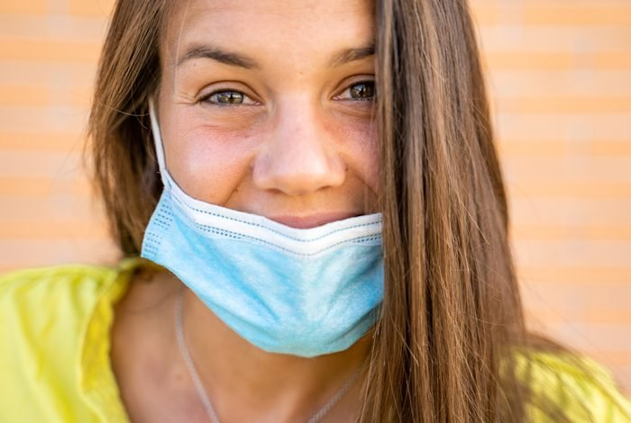 Smiling Young Woman Wearing Protective Face Mask Below Her Nose