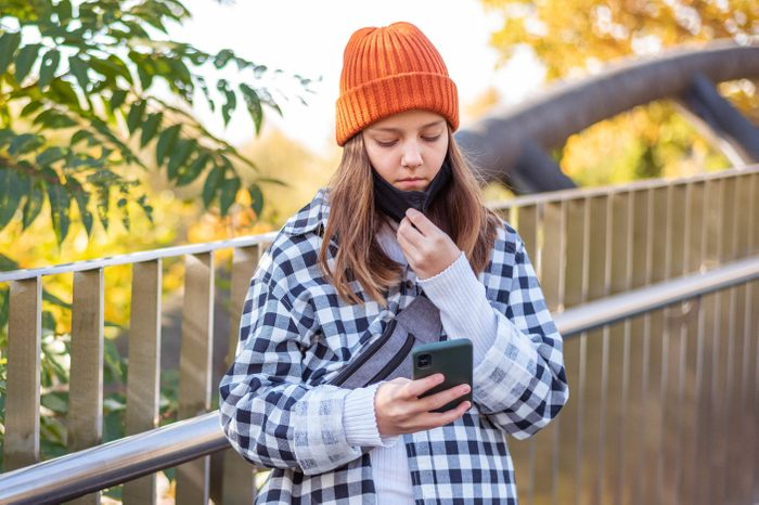 Cute girl wearing face mask under the chin while standing on the bridge and texting